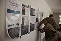 U.S. Soldiers with Georgia Agribusiness Development Team III, Regimental Combat Team 7 tape educational posters to a wall while teaching a veterinary class to staff members with an Afghan directorate 130424-M-QZ858-043.jpg