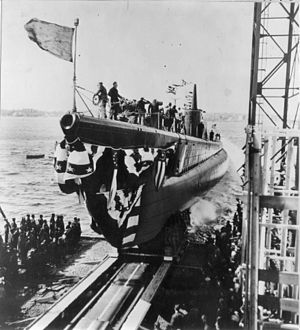 The crew of the Blackfish (SS-221) salute the colors as she is sliding down the launching ways at the Electric Boat Co.