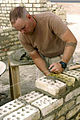 US Navy 041028-M-9529D-004 Seabee Builder 3rd Class Eddy Williams, assigned to Naval Mobile Construction Battalion Two Three (NMCB-23), levels bricks together during the construction an Iraqi Outreach Center in Al Asad, Iraq.jpg