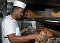 US Navy 041124-N-1205W-003 Culinary Specialist 3rd Class Stephen Green removes a turkey from an oven during the preparation for a Thanksgiving Day meal aboard the conventionally powered aircraft carrier USS John F. Kennedy (CV.jpg