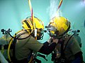 US Navy 050303-A-4697M-001 Lt. Bill Butler, left, promotes Lt. Christopher Steele at the bottom of the 15-foot Open Tank at Naval Diving and Salvage Training Center, Panama City, Fla.jpg