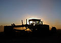 US Navy 070606-F-8678B-094 A grader is silhouetted in the sunset at Bradshaw Field Training Area.jpg