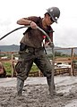 US Navy 070912-F-8678B-080 Builder Constructionman Lauren M. Nikaido, attached to Naval Mobile Construction Battalion (NMCB) 4, uses a concrete vibrator to ensure concrete is even and free of air bubbles during an overhead conc.jpg
