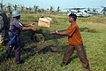US Navy 071128-N-7955L-110 A Bangladesh military member passes a box of blankets to a local resident.jpg