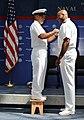 US Navy 110422-N-5328N-863 Center for Information Dominance Corry Station Command Master Chief Christopher Thompson stands on a stool to pin chief.jpg