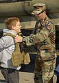 US Navy 111008-N-AP176-055 A Sailor assigned to Riverine Squadron (RIVRON) 1 puts a protective vest on a visitor at the RIVRON static display durin.jpg