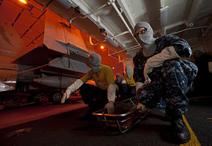 US Navy 111219-N-DR144-078 Airman Dennis Maughan and other stretcher bearers prepare to evacuate casualties during a general quarters drill in the.jpg