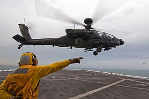 US Navy 120127-N-PB383-001 A Sailor guides a helicopter off the flight deck.jpg