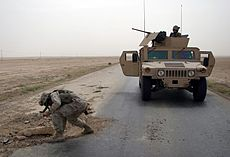 US soldier checks pothole for mines in Iraq May 2005.jpg