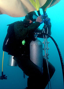 Underwater, near the reef, a US Naval diver in a scuba suit with mask, oxygen tank, and regulator, is attaching a large, upside-down beige bag to braided metal chain.