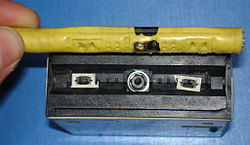 Dismantled vampire tap. Central metal-tipped insulated spike contactscable core; smaller spikes contact cable shield. Note black mark oncable sheath indicating suitable location for transceiver.