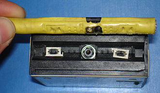 Vampire tap - Dismantled vampire tap. Central metal-tipped insulated spike contacts cable core; smaller spikes contact cable shield. Note black mark on cable sheath indicating suitable location for transceiver.