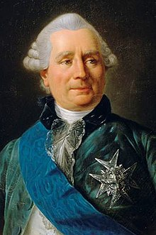 Middle-aged, white-haired man wearing a blue velvet jacket, white shirt, and a chivalric order pinned to his jacket