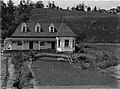 View of a two-story house with a broken window visible (AM 77155-1).jpg