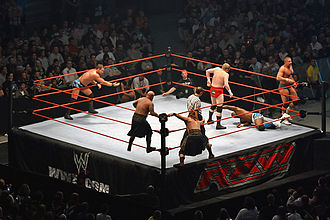 Tag team - Action in a triple threat tag team match for the WWE World Tag Team Championship. Shelton Benjamin (on the mat) from The World's Greatest Tag Team has been isolated in the corner of champions Cade and Murdoch, well away from partner Charlie Haas; either of these teams can tag in the third team, The Highlanders