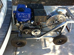 Winch - Example of winch designed for wakeboarding. These winches consist of a small four-cycle gasoline engine, clutch, and spool all housed inside of a steel frame. A rider is towed rapidly toward the winch as the rope winds around the spool.