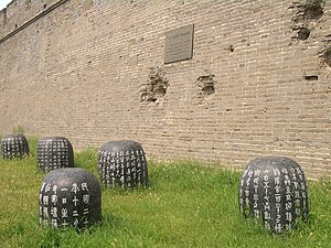 Marco Polo Bridge Incident - Damage from the Japanese shells on the wall of Wanping Fortress is marked with a memorial plaque now. The text on the stone drums below summarizes the history of the war that followed the incident
