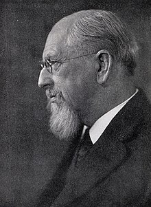 Portrait black and white photograph showing Dall's left profile. Dall's balding head, beard and glasses are shown and is wearing a serious expression on his face. He is wearing a dark coat and suit with a white shirt and a dark tie.