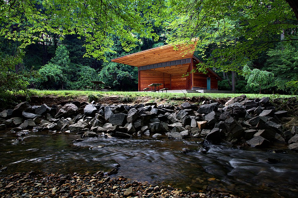 A small, boxy, wooden stage with a trapezoidal overhang stands in the center of meadow. In the foreground is a running stream with a stone embankment.