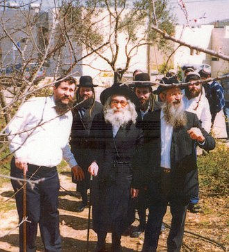 Arutz Sheva - Arutz Sheva Chairman Ya'akov Katz (front left) and founder Zalman Baruch Melamed (front right) during a visit of Rebbe Pinchas Menachem Alter (center) to Beit El in 1990
