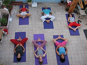 Hatha yoga - Students in a Hatha Yoga class practising the reclining bound angle pose, sometimes called bound butterfly pose
