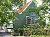 Houten boerderij, achter het woonhuis een vierkante stal met hoog dak