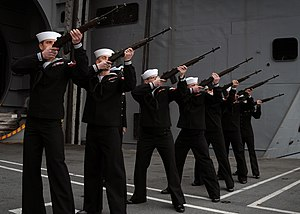 Three-volley salute - Sailors of the United States Navy, armed with M14s, form a rifle party and fire a volley salute on the deck of the aircraft carrier USS ''Abraham Lincoln'' during a burial at sea ceremony.