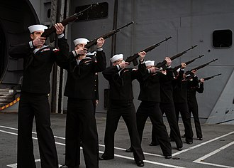 Three-volley salute - Sailors of the United States Navy, armed with M14s, form a rifle party and fire a volley salute on the deck of the aircraft carrier USS Abraham Lincoln during a burial at sea ceremony.