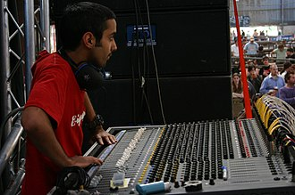 Live sound mixing - A monitor engineer and console at an outdoor event