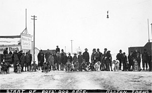 American Dog Derby - Start of Boys Race with each team consisting of one boy, one sleigh, and one dog.