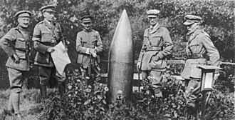 Unexploded ordnance - British and Belgian officers stand beside an unexploded German shell in Flanders, during the First World War.