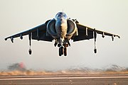 Front-view of grey jet aircraft executing a hover. The huge engine inlets are on both sides of the fuselage