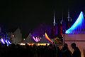 2013 Weihnachtsmarkt Am Küchengarten in Linden, Hannover (06) Blick über die Menschenmenge zwischen den Zelten zu den farbig illuminierten drei warmen Brüdern der Stadtwerke enercity.jpg