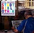2015-04-20 575 Jahre Stadtbibliothek Hannover, Aufkleber vor Zeitungsleser.jpg