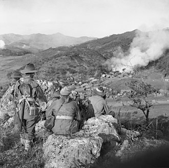 Australia in the Korean War - Troops from C Company, 3 RAR, watch for the enemy while a village in the valley below burns in November 1950