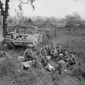 51st (Leeds Rifles) Royal Tank Regiment - Churchill tank crews of HQ Troop, 51 RTR share out rations near their camouflaged vehicles before going into action in support of the 1st Canadian Division, Italy, 17 May 1944.