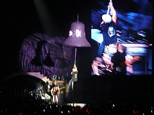 "Brian Johnson - Johnson hangs on to a bell while performing the song ""Hells Bells"""