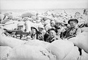 Soldiers wearing helmets sit in a sandbagged position near a machine gun