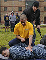 A U.S. Sailor, in yellow shirt, with the security department of the aircraft carrier USS Nimitz (CVN 68) subdues a mock assailant after being sprayed with pepper spray during a security academy qualification 130208-N-KE148-022.jpg