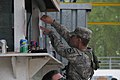 A U.S. Soldier with Alpha Troop, 1st Squadron, 38th Cavalry Regiment, 525th Battlefield Surveillance Brigade hangs a flyer on a shop stand during a Kosovo Force (KFOR) mission rehearsal exercise (MRE) at 130507-A-QC664-010.jpg