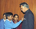 A child from the National Foundation for Communal Harmony pinning a flag to the Union Home Minister, Shri Shivraj Patil, on the occasion of the National Flag Day, in New Delhi on November 25, 2005.jpg