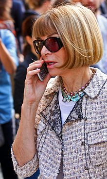 A woman with brownish hair, lit by the sun from outside the top right of the image, is seen from her front left. She is wearing a light-colored short-sleeved collared jacket with elaborate jewelry, a white top beneath it, and sunglasses. In her right arm she is holding a cell phone to her mouth; she is apparently in the midst of a conversation