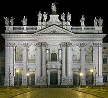 Ornate facade of the basilica at night with columns, main door, and statues of the twelve Apostles on the roofline, with a Latin inscription below them