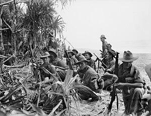 Australische Infanteristen, die an einem Flussufer ruhen, bevor sie im Januar 1945 japanische Stellungen in der Nahe von Matapau angreifen