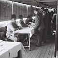 BRITISH IMMIGRANTION OFFICIALS CHEKING PASSPORTS AND CERTIFICATES OF IMMIGRANTS FROM GERMANY ON BOARD OF THE SHIP ANCHORING OFF JAFFA PORT. פקידי עלייD820-016.jpg