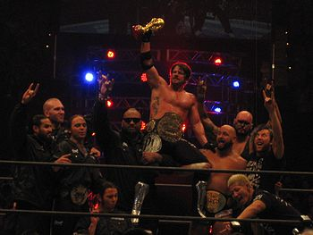 Ten members of the Bullet Club group celebrate in a professional wrestling ring. Several are using a hand gesture, extending the index and little finger, with the tips of the renaming fingers touching.