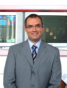 A photograph of a man with dark hair and a cleft chin wearing glasses, a grey suit, and a colourful tie while looking at the viewer and smiling