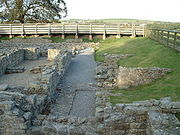 The ruins of a building.  The remains of stone walls up to about 1-foot (0.3m) are all that remains.