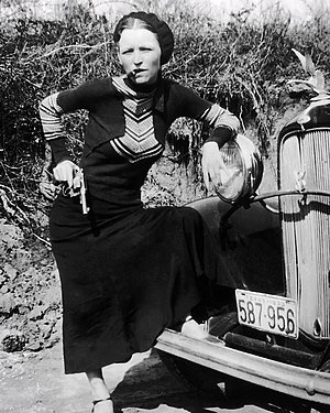 "Bonnie and Clyde - Parker's playful pose with a cigar brands her in the press as a ""cigar-smoking gun moll"" when police find the undeveloped film in the Joplin hideout"