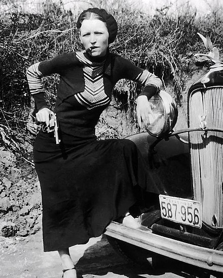 "Parker's pose with a cigar and gun gained her an image in the press as a ""cigar-smoking gun moll"" after police found the undeveloped film in the Joplin house BonnieParkerCigar1933.jpg"